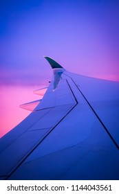 Aeroplane wing against purple/pink flying in the sky
