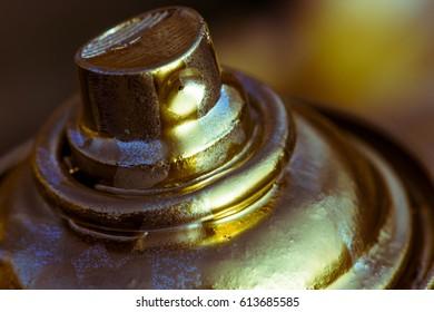 Aerosol paint, gold color, close-up.