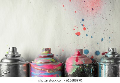 aerosol paints on a dirty gray background with stains of paint.