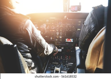 Aerospace, transport and people Two pilots dressed in uniform flying jet airliner on sunny day sitting inside aircraft cockpit surrounded by equipment. Selective focus on captain's hand on power lever