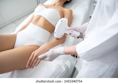 Aesthetic body treatment. Cropped head top angle portrait of young slender careful woman in underwear having professional laser epilation procedure of arm