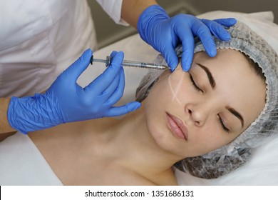 Aesthetic cosmetology. Facelift in spa salon. Beautician doing injection girl in cheeks. Smoothing of mimic wrinkles. Close-ups