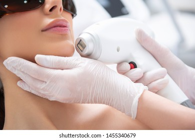 Aesthetic face treatment. Close up face down portrait of young careful woman having laser hair removal procedure of chin zone by specialist in cosmetic center