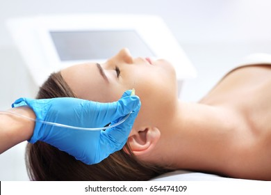 Aesthetic medicine, facial skin scraping. The doctor of aesthetic medicine performs a facial skin scraping treatment with a syringe.