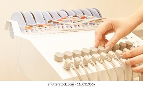 aesthetic salon spa procedure. adjustment. anti cellulite treatment device setting. electrostimulation woman body machine setup.