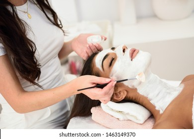 Aesthetics applying a mask to the face of a beautiful woman in modern wellness center. Beauty and Aesthetic concepts.