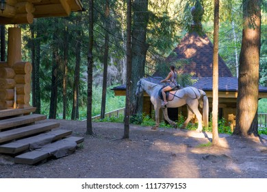 AFANASOVO, MOSCOW REGION/RUSSIA – AUGUST 8, 2015: Girl rides on horseback among trees against wooden chapel background on August 8, 2015 in Afanasovo.