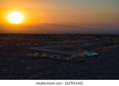 Afar Region, Ethiopia - January 01, 2019: Safari car going to the Erta Ale Volcano in Afar Region, Ethiopia at sunset, moving over the Danakil desert.
