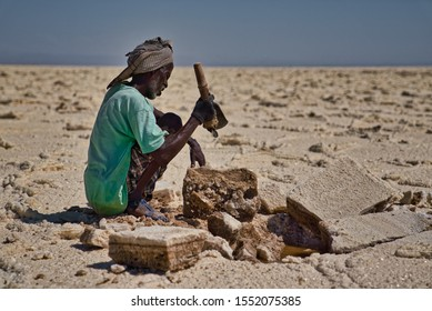 Afar Region, Ethiopia - January 03, 2019: Local man with turban working on a salt mine trying to get out salt from the rocks in the desert, in Afar Region, Ethiopia.
