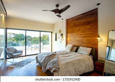 Afeq / Israel - Jan 14 2020:Master bedroom, king-size bed with wood-backed, hanging lamps, Ceiling Fan, wooden dressers, large window, balcony and armchair