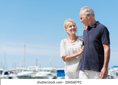Affectionate attractive mature couple at the sea standing smiling into each others eyes in front of a marine harbour