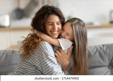Affectionate beautiful young woman cuddling small preschool child daughter, feeling happiness. Cute little kid girl embracing loving mommy, feeling thankful, enjoying tender sweet time at home.