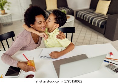 Affectionate black boy kissing his mother after finishing homework with her help at home.