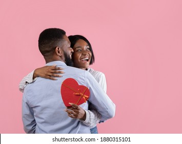 Affectionate black couple with Valentine's Day gift embracing on pink studio background, copy space. Attractive African American guy and his girlfriend celebrating lover's holiday