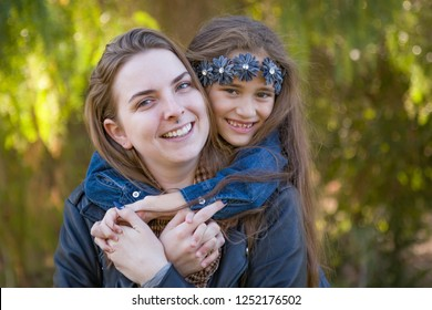 Affectionate Caucasian Mother and Mixed Race Daughter Portrait Outdoors.