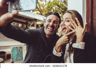 Affectionate couple announcing their engagement with selfies while sitting at cafe. Happy couple taking a selfie and showing off their wedding ring at coffee shop.