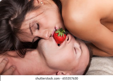 Affectionate couple eats strawberry while kissing. Love kiss of young sexy heterosexual sensual couple. Love you. Erotic moments. Intimate. Love story. Healthy eating concept. Dieting. Fashion concept