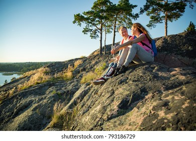 Affectionate couple hiking on top of the rock. Sitting, drinking champagne , celebrating. Man and woman enjoying scenic view in Finland
