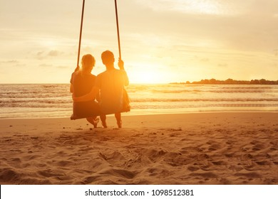 Affectionate couple in love sitting on rope swing in luxury idyllic paradise sunset sea beach of Thailand. Honeymoon vacation on tropical island near ocean in luxurious resort . Copyspace.