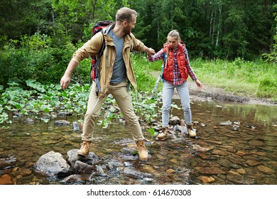 Affectionate couple passing river in the forest