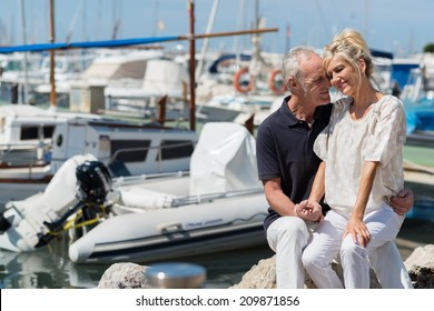 Affectionate couple relaxing in a small boat harbour with the wife sitting on her husbands lap as they nuzzle lovingly