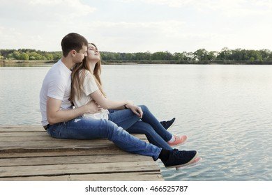 Affectionate couple sits on the mooring lake