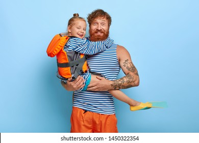 Affectionate father carries small red haired daughter in lifejacket and flippers, enjoy recreation and swimming in sea, have rest at beach. Cute girl embraces dad with love. Family and rest concept