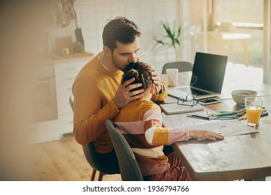 Affectionate father kissing his small daughter while working at home.