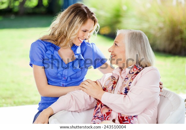 Affectionate granddaughter and grandmother looking at each other on nursing home porch