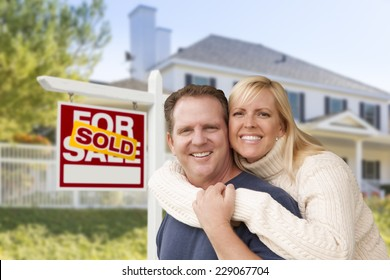 Affectionate Happy Couple in Front of New House and Sold For Sale Real Estate Sign.