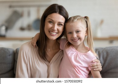 Affectionate happy single mom and cute little child daughter embracing bonding looking at camera sitting on sofa, young foster care parent mum hug small kid girl cuddling at home, family portrait