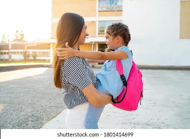 Affectionate hug mother holding her daughter in arms , after school with backpack