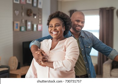 Affectionate mature African couple laughing and enjoying a playful moment while dancing together in their living room at home