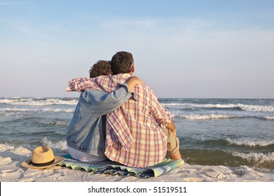 Affectionate mature couple sitting close together at sunset on the beach in the sand, gazing out to sea.