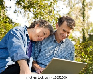 Affectionate mature couple at their laptop, outdoor setting