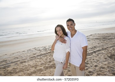 Affectionate mid-adult Hispanic couple standing on beach