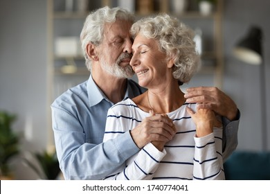 Affectionate middle aged mature bearded man cuddling senior smiling wife, enjoying romantic sweet moment at home. Happy older 60s family couple show love care devotion, retirement relationship.