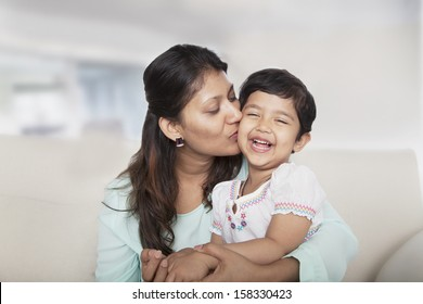 Affectionate mother holding and kissing her daughter