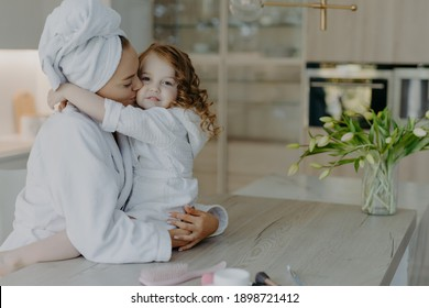 Affectionate mother wearing dressing gown wrapped bath towel on head embraces and kisses with love her small daughter pose together at home against cozy interior feel refreshed after taking shower