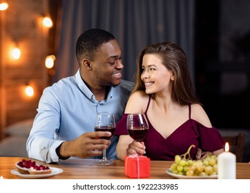 Affectionate Multicultural Couple Enjoying Date In Restaurant, Celebrating Valentine's Day Together, Interracial Lovers Having Romantic Dinner, Drinking Wine And Smiling To Each Other, Free Space