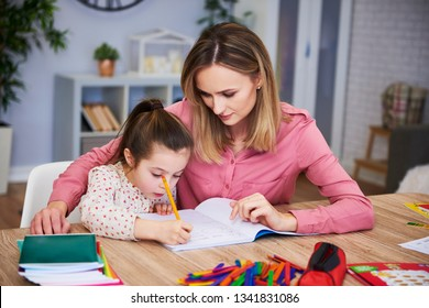 Affectionate mum helping her daughter with difficult homework