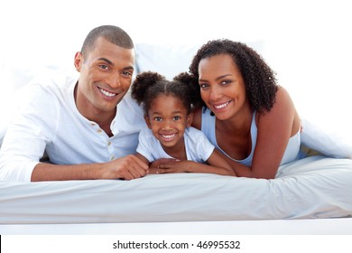 Affectionate parents and their daughter lying on a bed smiling at the camera