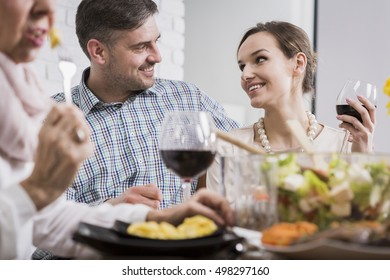 Affectionate portrait of a young couple smiling at each other and drinking wine at a table
