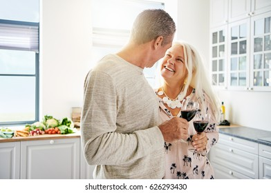 Affectionate senior couple drinking wine in the kitchen together with focus to the smiling attractive wife looking lovingly at her husband