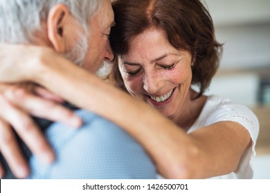 Affectionate senior couple in love standing indoors at home, hugging.