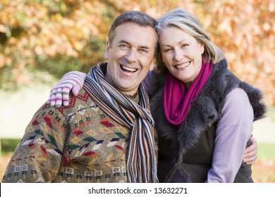 Affectionate senior couple on autumn walk with trees in background