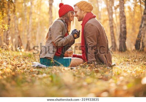Affectionate sweethearts sitting face to face on autumn leaves