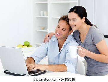 Affectionate woman looking at her boyfriend working on the laptop in the kitchen