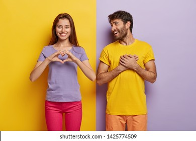 Affectionate woman shows heart gesture, says be my valentine to boyfriend, confesses in love, touched handsome guy keeps both hands on heart, enjoys love story with girlfriend. Relationship concept