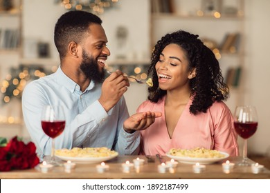Affectionate young black couple having dinner, guy feeding his girlfriend with pasta. Cute lovers having romantic date, flirting, having fun, celebrating St Valentine's Day or holiday